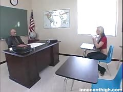 Blonde is kneeling down in front her teacher and starting to suck